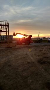 Workers at the Alt Oil Company jobsite capture a beautiful sunset behind a piece of machinery after a long day of work.